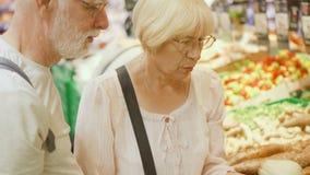 Старшие покупки пар в гастрономе Стоять в vegetable отделе выбирая свежие корни сток-видео