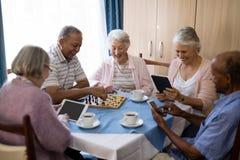 Старшие друзья играя шахмат и используя технологию на таблице стоковые изображения