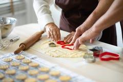 Старшие руки делают печенья стоковые фото