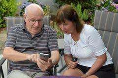Старшие текстовые сообщения чтения пар на мобильном телефоне Стоковое Изображение RF