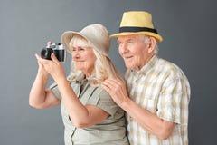 Старшие туристы в положении студии шляп пляжа на сером человеке обнимая женщину фотографируя с камерой стоковое фото