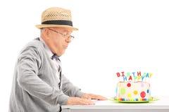 Старшие дуя свечи на его именнином пироге Стоковые Фотографии RF