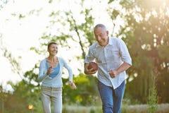 Старшие люди играя американский футбол Стоковые Изображения RF
