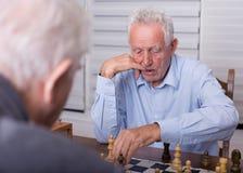 Старшие люди играя шахмат Стоковые Изображения RF