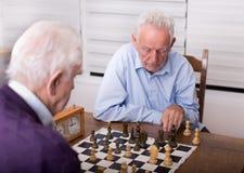 Старшие люди играя шахмат Стоковое Фото