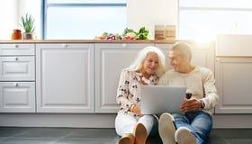 Старшие люди используя компьтер-книжку в кухне стоковые фотографии rf