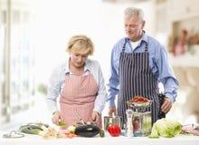 Старшие пары варя в кухне Стоковое Изображение
