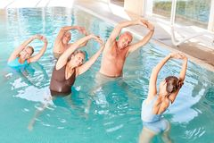 Старшии в бассейне делая аэробику воды в мастерской стоковое изображение rf