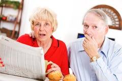 Старшии: Пары сотрясенные что-то в газете стоковое фото