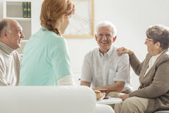 Старшии сидя с медсестрой стоковое изображение