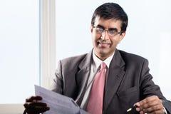Старший администратор в офисе небоскреба, читая контракты Стоковые Изображения RF