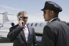 Старший бизнесмен вне частного самолета на звонке chauffeur Стоковые Изображения RF
