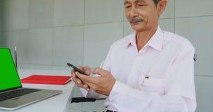 Старший бизнесмен используя мобильный телефон в офисе сток-видео