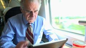 Старший бизнесмен коммутируя на поезде используя Digita видеоматериал