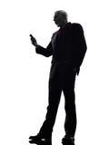 Старший бизнесмен на силуэте телефона сердитом Стоковая Фотография