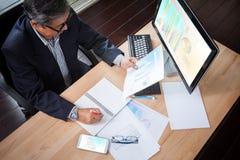 Старший бизнесмен смотря к отчету о диаграммы бумаги дела в ha Стоковая Фотография RF