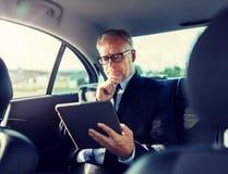 Старший бизнесмен с ПК планшета управляя в автомобиле стоковые фотографии rf