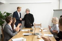 Старший босс повышая работника тряся руки объединяется в команду аплодировать на Стоковая Фотография RF