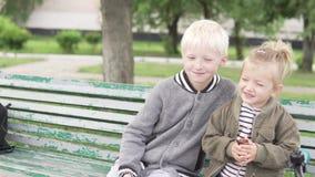 Старший брат нежно обнимает более молодую сестру в парке видеоматериал