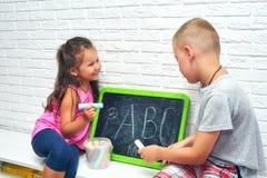 Старший брат учит, что сестра пишет письма в летних отпусках стоковые фотографии rf