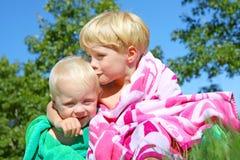 Старший брат целуя младенца в пляжных полотенцах Стоковые Фото