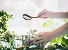 Старший варить сиропа цветка Сахар женской руки лить от ложки в баке с Elderflowers на кухонном столе Стоковые Изображения