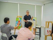 Старший взрослый учитель художника уча в комнате класса стоковое фото