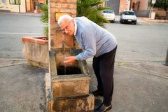 Старший выпивать от фонтана стоковая фотография