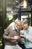 Старший выпивать Tean после полудня пар ослабляет концепцию Стоковые Изображения