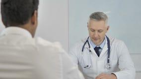 Старший доктор Advising Пациент, помогая с вопросами здравоохранения
