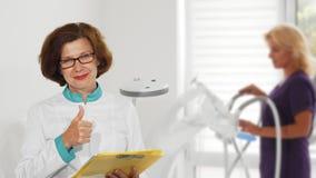 Старший женский доктор показывая большие пальцы руки вверх представляя на больнице стоковое фото