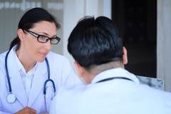 Старший женский доктор советует с молодым пациентом сидя на докторе  стоковая фотография