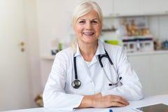 Старший женский доктор усмехаясь на камере стоковая фотография rf