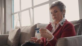 Старший женский покупатель делая онлайн сделку используя смартфон и кредитную карточку акции видеоматериалы