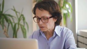 Старший женский профессионал в голубом shitr работая на компьтер-книжке акции видеоматериалы