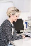 Старший женский работник сидя на столе смотря бумагу дела стоковое фото