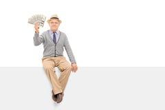Старший джентльмен держа деньги усаженный на панель Стоковая Фотография