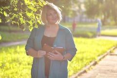 Старший женщины в парке с книгой Стоковое Фото
