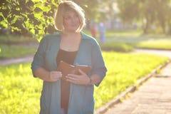 Старший женщины в парке с книгой Стоковые Изображения