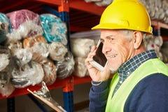 Старший знонит по телефону с мобильным телефоном в складе ковра стоковые фото
