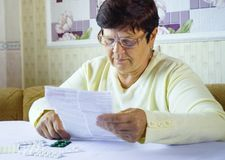 Старший информационный лист чтения женщины предписанной медицины сидя на таблице дома стоковое изображение