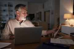 Старший испанский человек проверяя его финансы онлайн дома используя ноутбук вечером стоковое изображение