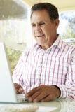 Старший испанский человек используя компьтер-книжку в домашнем офисе Стоковые Фото