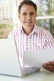 Старший испанский человек работая в домашнем офисе Стоковое фото RF