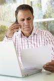 Старший испанский человек работая в домашнем офисе Стоковая Фотография