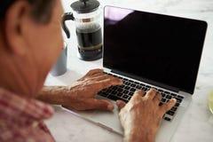 Старший испанский человек сидя дома используя компьтер-книжку Стоковые Изображения RF