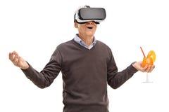Старший используя шлемофон VR и держащ коктеиль стоковое изображение rf