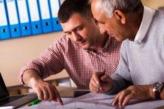 Старший и молодой архитектор работая совместно на проекте в офисе Стоковые Фотографии RF