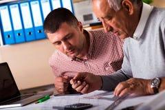 Старший и молодой архитектор работая совместно на проекте в офисе Стоковые Фото
