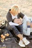 Старший кавказский супруг лежа на коленях и шотландке жены, шампанском и плодах на пляже песка стоковые изображения rf